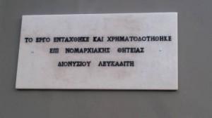 Η μαρμάρινη πλάκα που γράφει (ΟΡΘΩΣ) «Το έργο εντάχθηκε και χρηματοδοτήθηκε επί Νομαρχιακής θητείας Διονυσίου Λευκαδίτη»